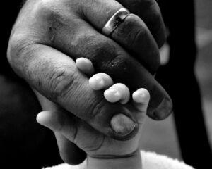 foto preto e branco de mão de pai com bebê